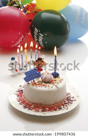 Birthday cake with burning candles and balloons - stock photo