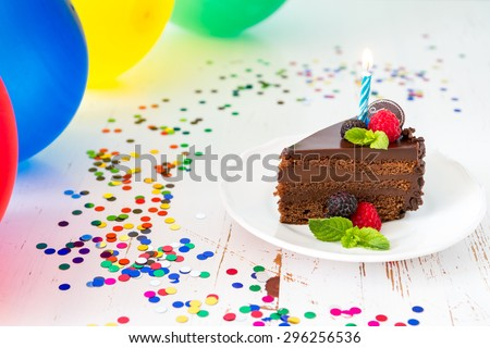 Birthday cake with candle, balloons, white wood background - stock photo