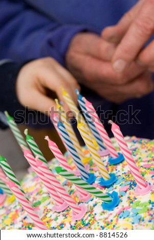 birthday cake with candles - old and young hands in background - stock photo