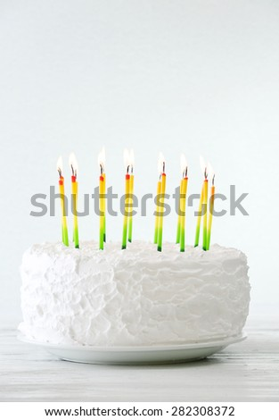 Birthday cake with candles on light background - stock photo