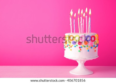 Birthday cake with candles on pink background. - stock photo