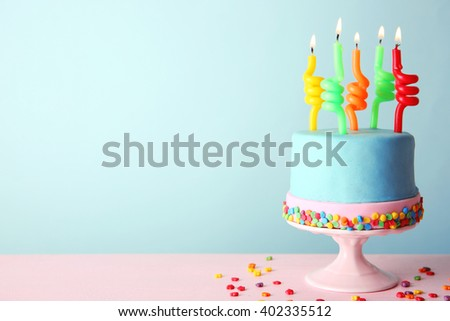 Birthday cake with candles on turquoise  background. - stock photo