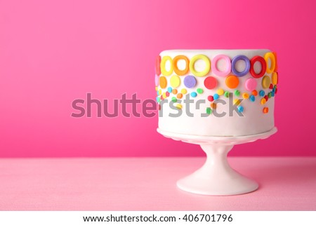 Birthday cake with colorful decorations on pink background. - stock photo