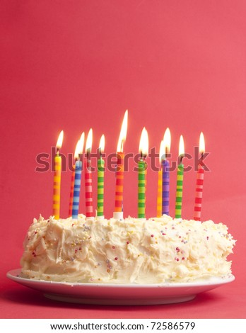 birthday cake with lots of cute striped candles shot on a red background - stock photo