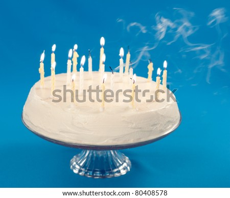 Birthday cake with smoke coming from blown out candles - stock photo