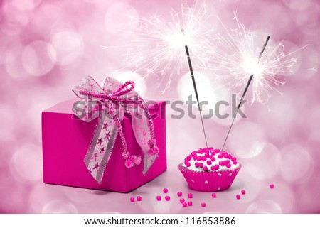 birthday cake with sparkler and  gift on a pink background - stock photo