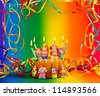 birthday cake with sugar clowns decoration and candles. Holiday background - stock photo
