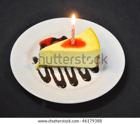 Birthday cheesecake with chocolate and raspberry sauce - stock photo