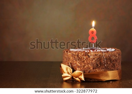 Birthday chocolate cake with burning candle as a number eight on brown background