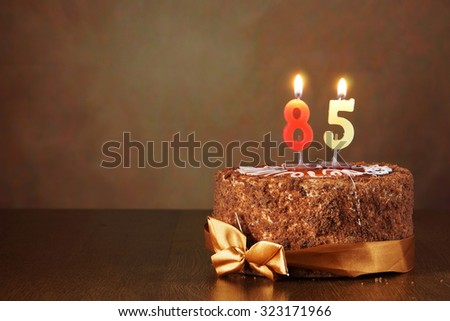 Birthday chocolate cake with burning candles as a number eighty five on brown background