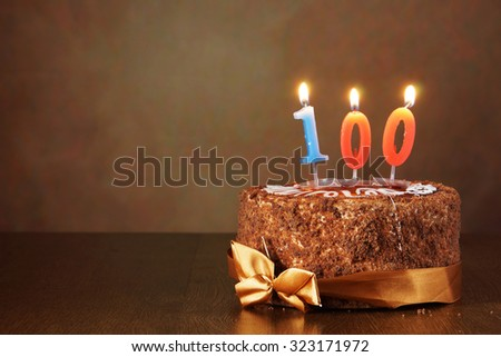 Birthday chocolate cake with burning candles as a number one hundred on brown background - stock photo