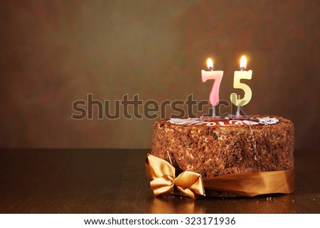 Birthday chocolate cake with burning candles as a number seventy five on brown background - stock photo