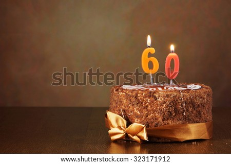 Birthday chocolate cake with burning candles as a number sixty on brown background