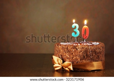 Birthday chocolate cake with burning candles as a number thirty on brown background
