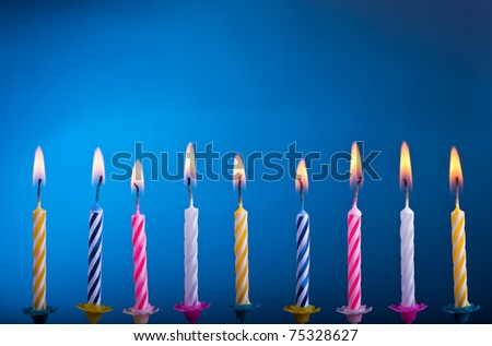 Birthday colour candles with fire on blue background