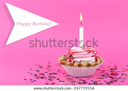 Birthday cup cake with candle and colorful stars on pink background - stock photo