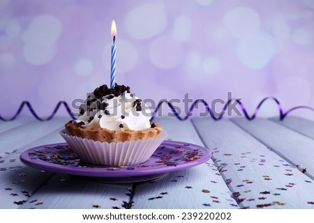 Birthday cup cake with candle on plate on color wooden table and light background - stock photo