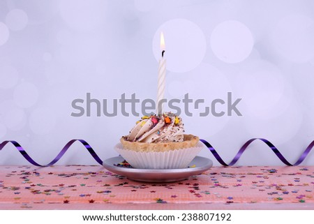 Birthday cup cake with candle with sparkles on plate on color wooden table and light background