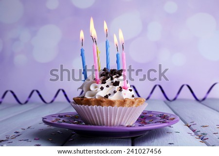 Birthday cup cake with candles on plate on wooden table and light background - stock photo