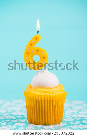 birthday cup cake with number six candle on blue background - stock photo