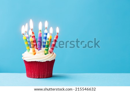 Birthday cupcake against a blue background - stock photo