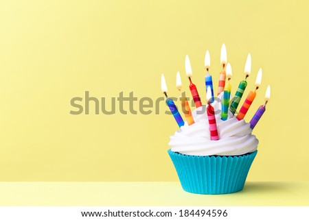 Birthday cupcake against a yellow background - stock photo