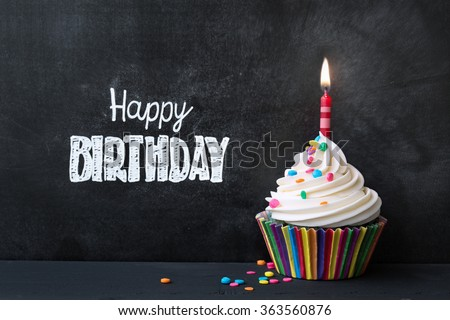 Birthday cupcake in front of a chalkboard - stock photo