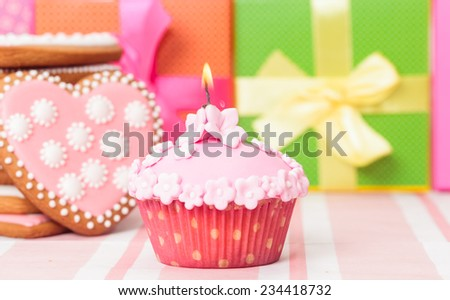 birthday cupcake with burning candle and presents
