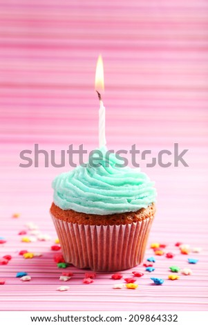 Birthday cupcake with butter cream on colorful background - stock photo