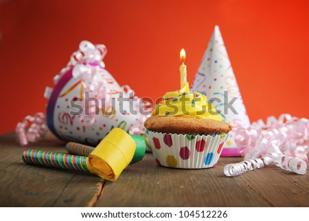 Birthday cupcake with candle and birthday hats in background - stock photo
