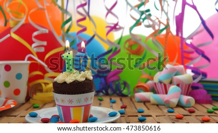 Birthday cupcake with candles burning on rustic wooden table with background of colorful balloons, plastic cups and candies with white wall in the background