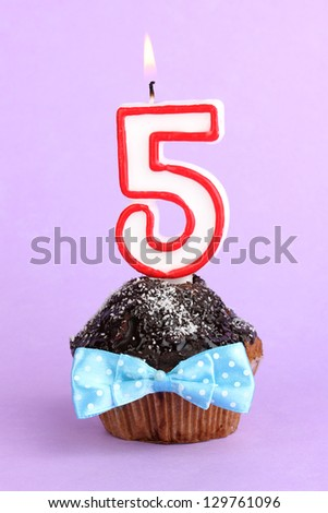 Birthday cupcake with chocolate frosting on lilac background - stock photo