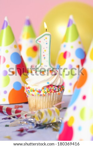Birthday cupcake with lit candle labeled number 1 with party hats and balloon in the background