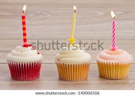birthday cupcakes with burning candles on wooden table - stock photo