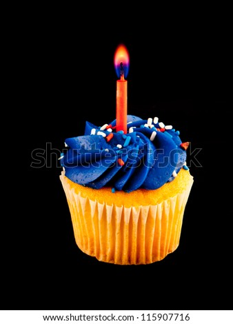 Birthday cupcakes with candles alight on a black background.