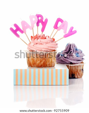 Birthday cupcakes with colorul latters on white background - stock photo