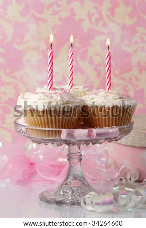Birthday cupcakes with soft fondant icing and candles - stock photo