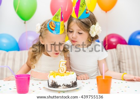 Birthday girl and her friend enjoying birthday party