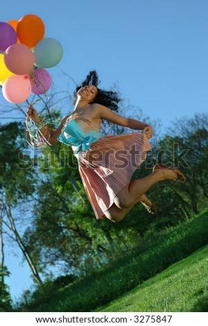 Birthday girl jumping for joy with her balloons - stock photo