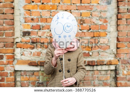 Birthday greetings. Thirty years. The girl costs against brick wall and covers the face with balloon. - stock photo