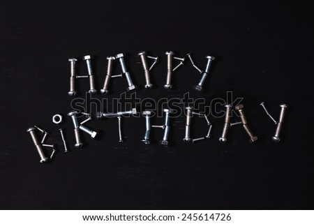 birthday of metal nuts and bolts on a black background - stock photo