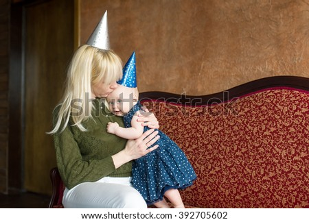 Birthday of the little girl. Mother embraces the daughter. - stock photo