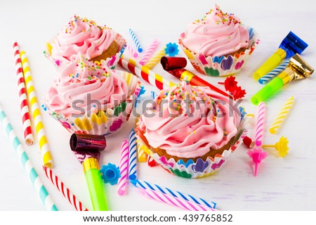 Birthday party concept with pink cupcakes. Colored striped drinking straws, birthday party candles and cupcakes with whipped cream. Birthday invitation background.