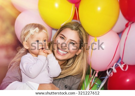 Birthday party of baby girl, cheerful little child with mother having fun outdoors with many colorful balloons, happy family life - stock photo