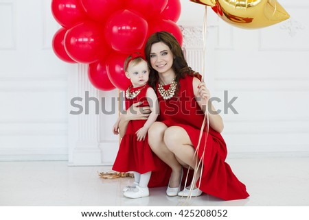 Birthday party of baby girl, cheerful little child with mother having fun with many red balloons, happy family life - stock photo
