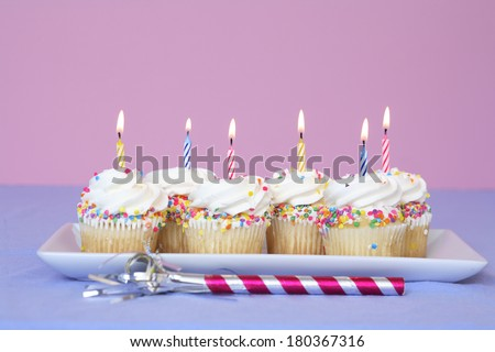 Birthday still life of cupcakes on white tray with lit candles on pink background - stock photo