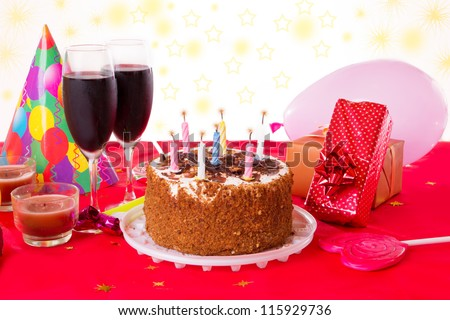 Birthday table with cake, candles, wine and gifts - stock photo