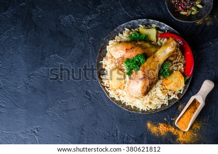 Biryani with chicken and potatoes in iron bowl on blask stone background. Selective focus - stock photo