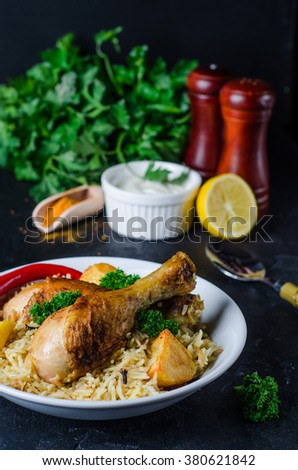 Biryani with chicken and potatoes in white bowl on blask stone background. Selective focus - stock photo
