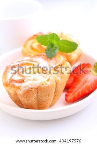 Biscuit cakes with curd filling decorated with strawberries and mint - stock photo